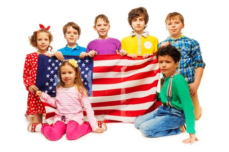 child boy: Group of seven kids sitting on their lap holding American flag, isolated on white background Stock Photo