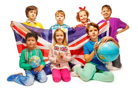 foreign national: Group of seven happy kids studying geography with globes and holding flag of Great Britain, isolated on white