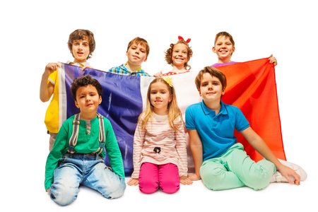 standing together: Group of age-diverse kids sitting with French flag isolated on white background Stock Photo