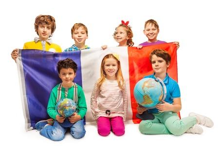 personas de pie: Siete alumnos que se sienta con globos, con bandera francesa, aislado en fondo blanco Foto de archivo