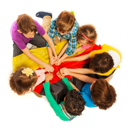 top seven: Top view of seven friends, boys and girls, holding their arms together above the flag of Germany, isolated on white background Stock Photo