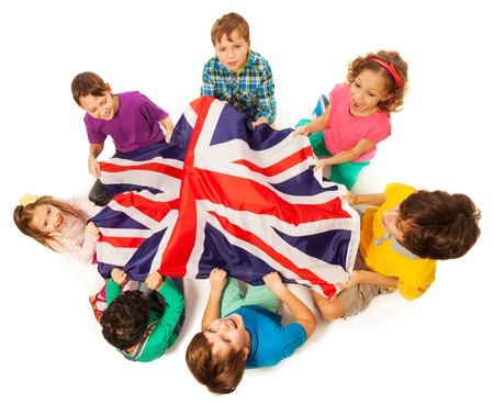 Top view of seven kids holding English flag in the middle of their circle, isolated on white background Foto de archivo