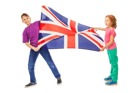 foreign nation: Two happy kids, boy and girl smiling and waving English flag, isolated on white Stock Photo