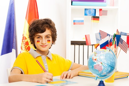 language school: German schoolboy writing at copybook with pencil in light classroom