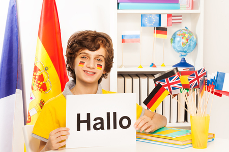 foreign national: Happy schoolboy with flags on cheeks learning German, holding sign with word Hallo, at the light classroom Stock Photo
