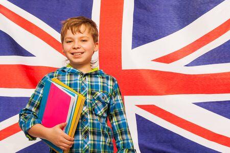 bandiera inglese: Scolaro sorridente con i libri di testo in mano in piedi contro la bandiera inglese