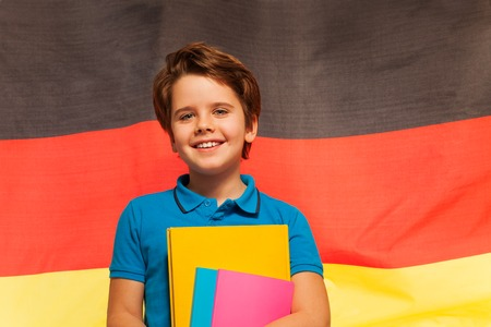 textbooks: Happy German schoolboy with textbooks in his hand standing against the waving flag of Germany