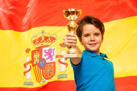 european championship: Happy boy with cup in his hand standing against waiving flag of Spain