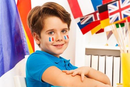 diligente: Retrato del colegial francés diligente con banderas en las mejillas sentado en el aula Foto de archivo