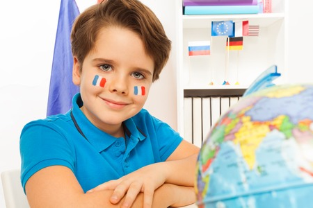 Cute French boy learning geography with the globe in the classroom Imagens