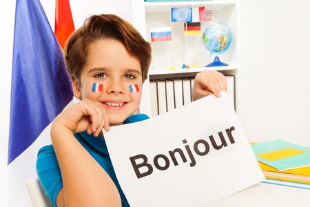 bonjour: Smiling French boy holding sheet of paper with printed word bonjour at the classroom