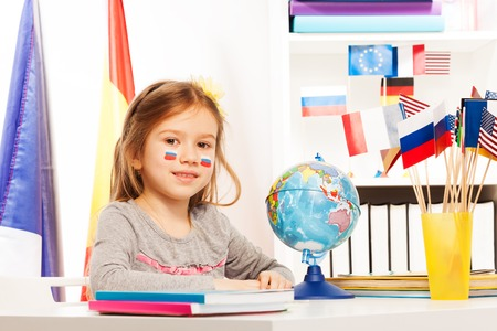 foreign nation: Russian schoolgirl sitting at the desk on geography lesson in the light classroom Stock Photo