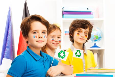 foreign nation: Three pupils with flags on their cheeks sitting in the class at the ecology lesson