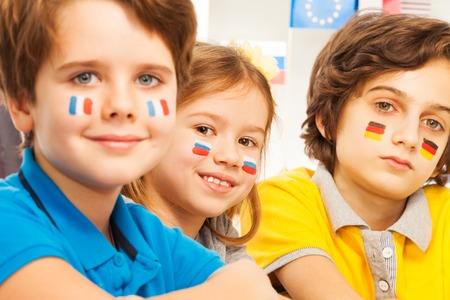 foreign country: Close-up photo of three cute children with flags on cheeks in language camp