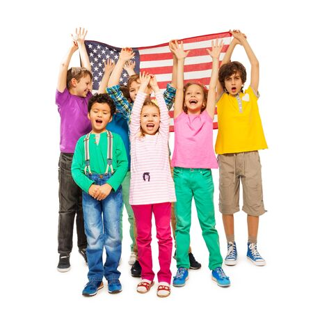 enveloped: Group of happy age-diverse children enveloped under American flag isolated on white background Stock Photo