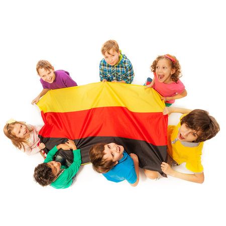top seven: Top view of seven happy kids holding German flag sitting around it, isolated on white background Stock Photo