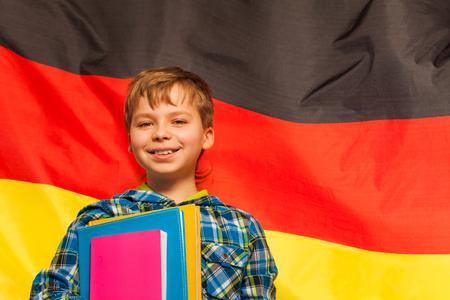 Colegial sonriente con los libros de texto de pie junto a la bandera de Alemania Foto de archivo