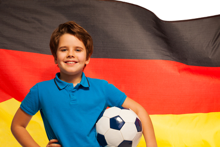 foreign nation: Happy young football player with ball under his arm standing against the waving flag of Germany