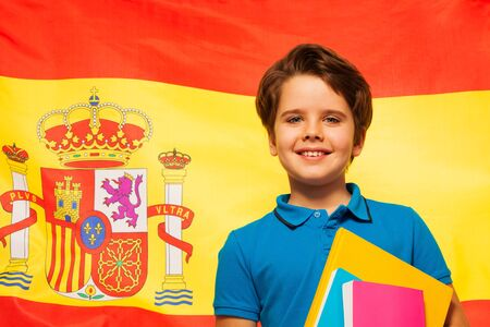 textbooks: Smiling schoolboy with his textbooks standing against the flag of Spain