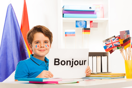 bonjour: Boy learning French sitting at the desk in the classroom holding sheet of paper with printed word bonjour Stock Photo