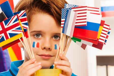 Gros plan image du jeune Français avec des drapeaux sur les joues se cachant derrière des drapeaux