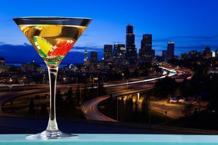 Światła: Martini glass with two dibs inside against the view of city skyline Zdjęcie Seryjne