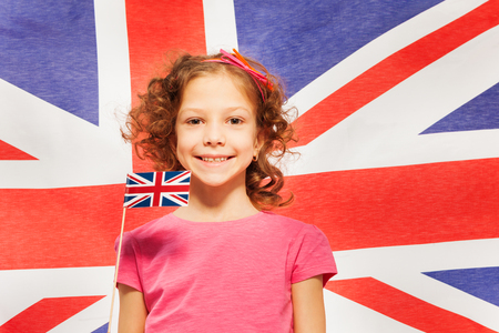 british girl: Funny curly-haired smiling girl with little pennon against British flag