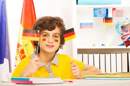 foreign country: German schoolboy holding two pennants in his hands, sitting at the desk in the light classroom Stock Photo