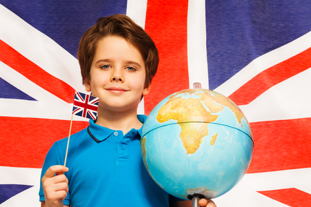 foreign nation: Proud English boy with little flag and globe at his hands standing in front of British flag Stock Photo