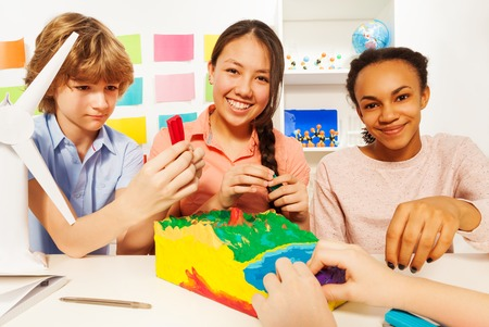 topographical: Three teenage kids creating topographical relief with modeling clay at the classroom Stock Photo