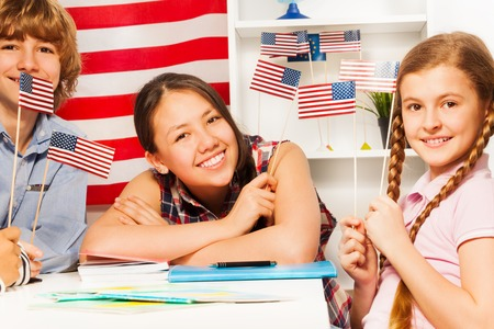 Three smiling teenage students, boy and girls, sitting with American flags at the class