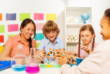 boy 15 year old: Four multi ethnic students studying chemistry with molecule model and flasks at the school laboratory