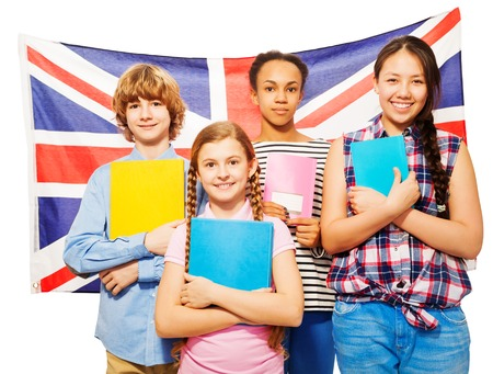 Four happy multiethnic teenage students standing against British flag, holding textbooks, isolated on white Stock Photo