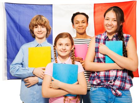 13 15 years: Four happy multiethnic teenage students with textbooks standing against French Flag, isolated on white