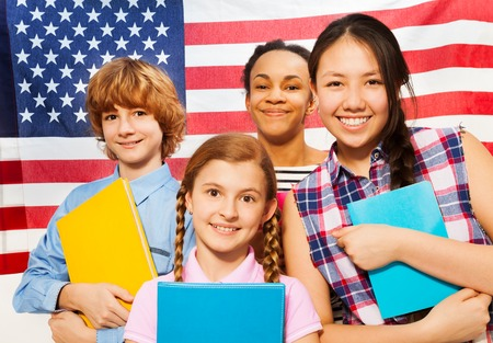 textbooks: Close-up picture of four smiling multiethnic teenage students standing with textbooks against American flag
