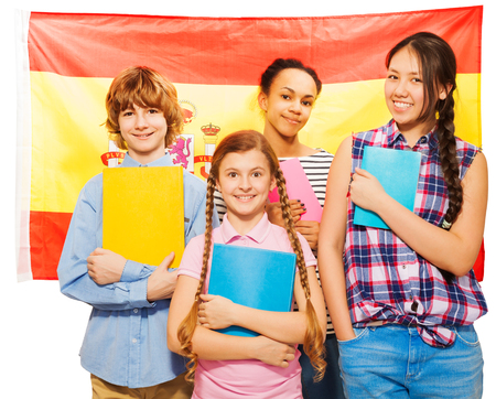 13 15 years: Four happy multiethnic teenage students standing against Spanish flag, holding textbooks, isolated on white