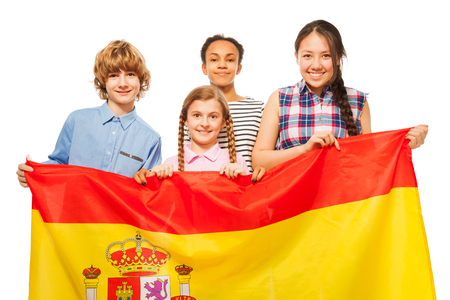 boy 15 year old: Group of four happy multiethnic teenage kids with flag of Spain, isolated on white