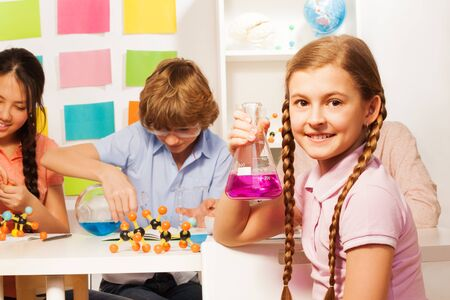 boy 15 year old: Cute schoolgirl with long plaits holding flask with pink reagent at the school laboratory