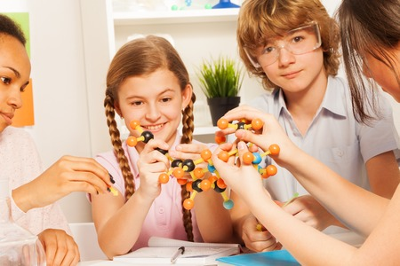 13 year old boy: Four students, teenagers, assembling atomic chain with molecular model at chemical laboratory