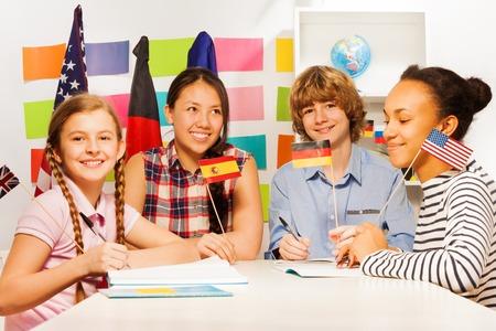 Vier multi-etnische tiener studenten zitten aan de balie, met Duitse, Spaanse en Amerikaanse vlaggen op de taalcursussen Stockfoto