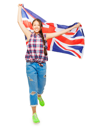 Smiling Asian girl walking and waving British flag isolated on white background