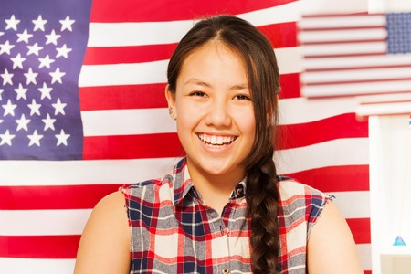 plait: Beautiful smiling teenage Asian girl with long plait against  the flag of United states of America Stock Photo