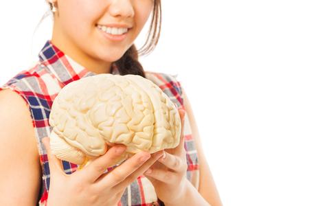 encephalon: Smiling girl holding cerebrum model in her hands, isolated on white background