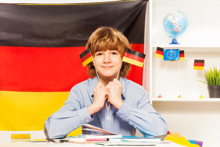 boy 15 year old: Caucasian teenage student with two flags of Germany sitting at the class