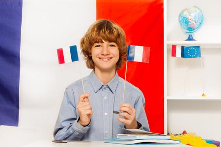 クラスでフランス語を学ぶ彼の手に 2 つのフラグを保持している 10 代の少年の笑顔 写真素材