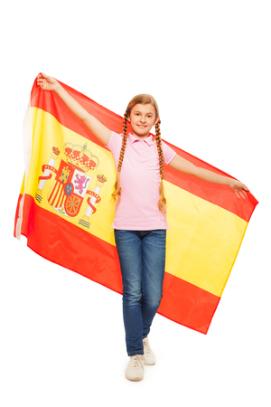 13 15 years: Beautiful young girl with two long plaits holding unfolded Spanish flag behind her back, isolated on white