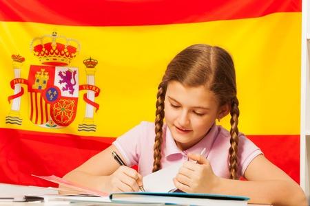 diligente: diligente estudiante adolescente, chica de raza blanca, escribiendo con una pluma en su cuaderno, bandera española detrás Foto de archivo