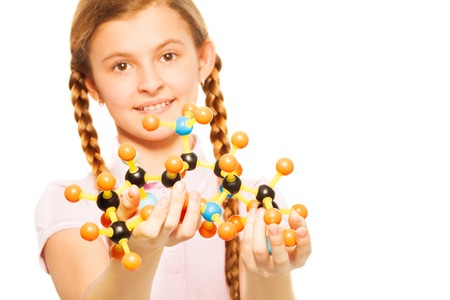 atomo: Retrato de colegiala adolescente con la estructura molecular en sus manos, aisladas sobre fondo blanco