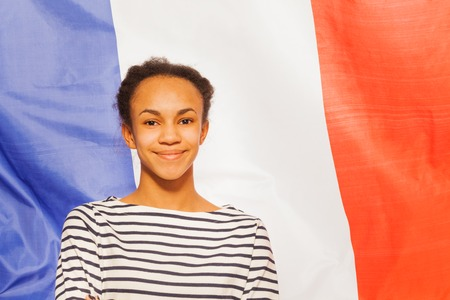 13 15 years: Portrait of beautiful African teenage girl in frock with French flag on background Stock Photo
