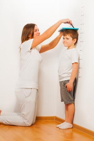 母は床に立っている子供として、ペンで線を指す白い壁に対して彼女の息子の身長を測定 写真素材